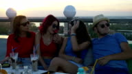 Group of friends on a rooftop bar having a chat and enjoying a drink video