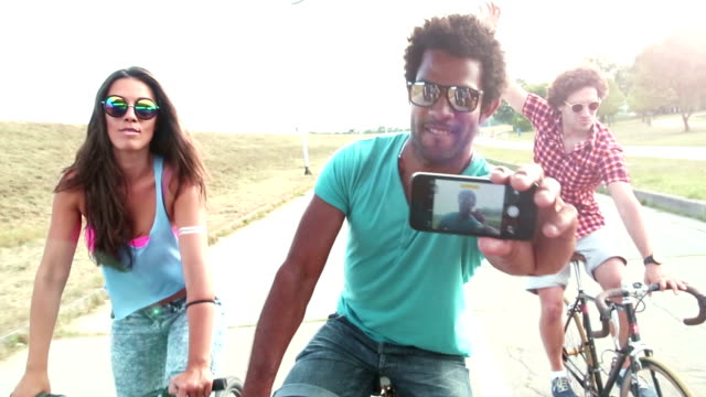 Group of friends on bikes smiling and taking selfies with phone video