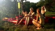 Group of friends resting in nature after riding a canoe video