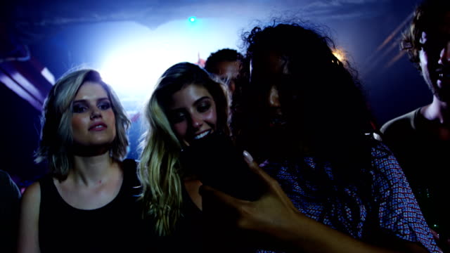Group of friends reviewing pictures on mobile phone at a concert 4k video