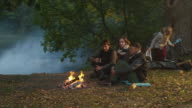 Group of friends sit in a forest near a lake next to a campfire with warm drinks while another girl steps out from a tent. video