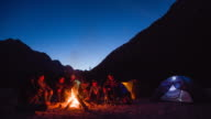 Group of friends sitting by the campfire, exchanging stories video