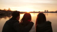Group of friends sitting on the edge of the lake and relaxing at sunset. video
