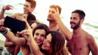 Group of friends taking selfies on the beach video