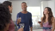 Group of friends talking in the kitchen at a party, waist up video