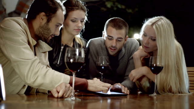 Group of friends uses tablet while drinks wine in rural farm-house, tuscany, italy, at night - slow-motion HD video footage video