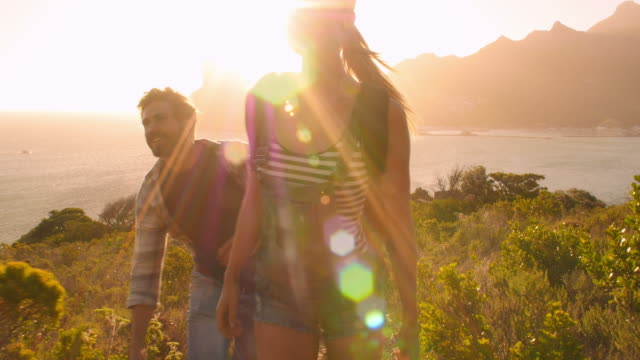 Group of friends walking along coastal path together video