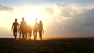 Group of friends walking on the beach at sunset video