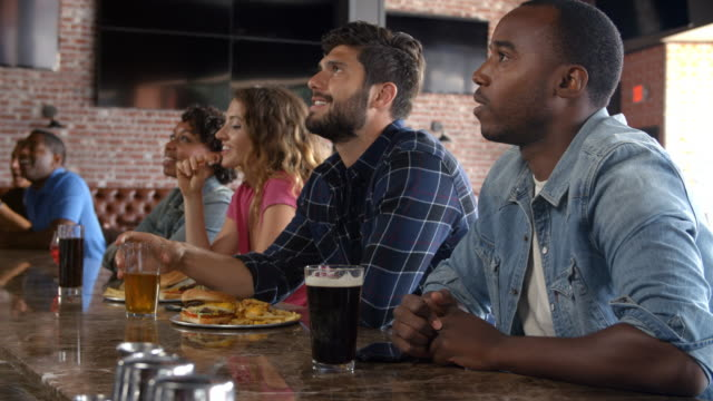 Group Of Friends Watching Game In Sports Bar On Screens video