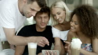 Group of friends watching photos on phone and laughing. video