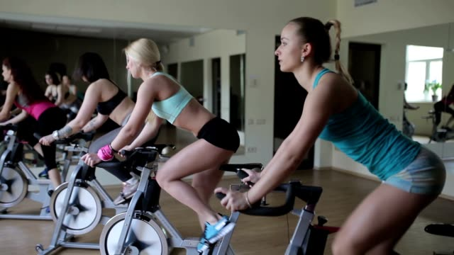 Group of girls using exercise bikes for training video