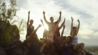 Group of happy adults together on top of a hill cheering. video