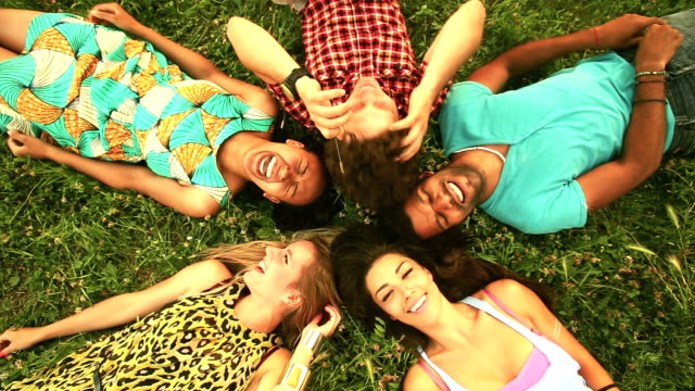 Group of happy friends forming a circle with their heads laying back on grass video