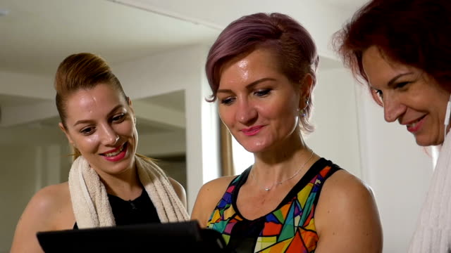 Group of happy women talking about fitness healthy lifestyle and sport using a digital trackers video