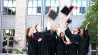 Group of high school graduates throwing caps in air video