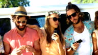 Group of hipster friends looking on their smartphone video