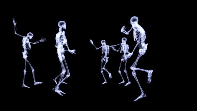 Group of human skeleton dancing on black background video