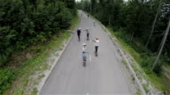 Group of longboard skaters driving on forest road aerial footage video