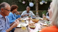 Group Of Mature Friends Enjoying Outdoor Meal In Backyard video