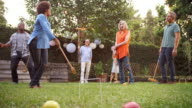 Group Of Mature Friends Playing Croquet In Backyard Together video