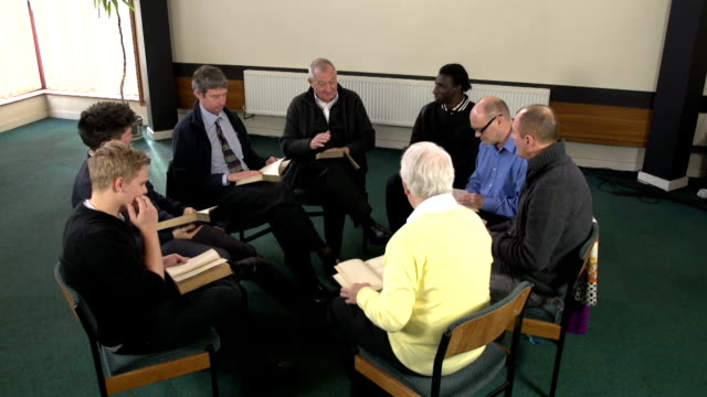 Group of Men studying a book or bible study video