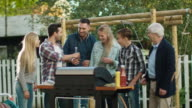 Group of Mixed Race People are Gathering around the Grill on Backyard before Family Dinner. video