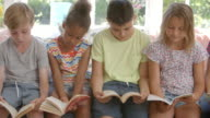 Group Of Multi-Cultural Children Reading On Window Seat video