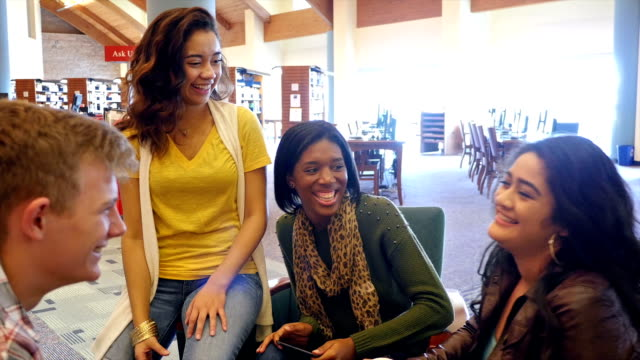 Group of multi-ethnic home school students talk and laugh with one another in a local public library video