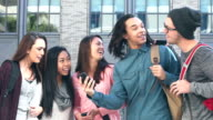 Group of multi-ethnic students gather round mobile phone video