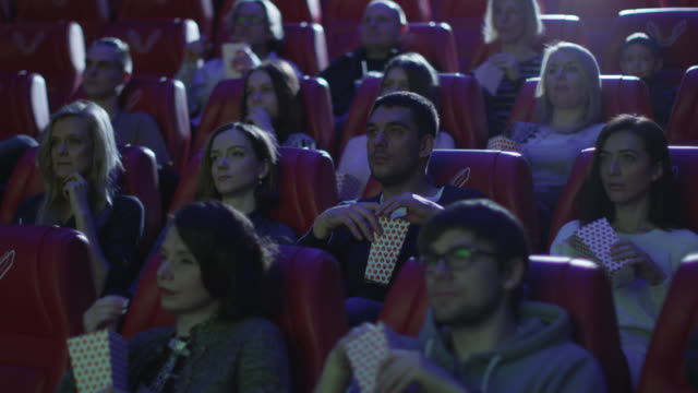 Group of people are scared while watching a horror film screening in a movie cinema theater. video