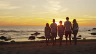 Group of People are Staying on the Beach and Together Watching Sunset video