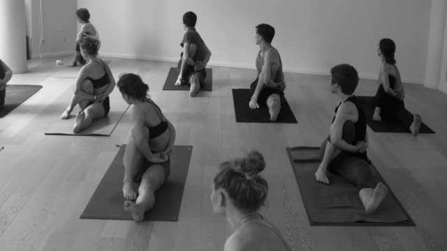Group of people doing yoga asanas in studio video