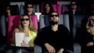 Group of people in 3D glasses watching a movie at cinema. Slider camera movement video