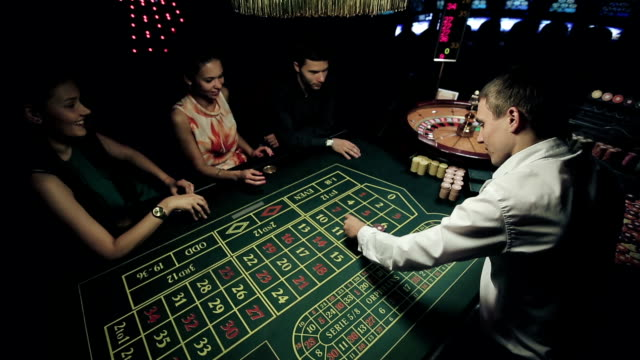 Group of people in casino playing roulette video