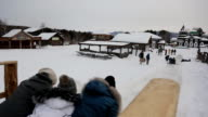 Group of people moves along icy surface on piece of cardboard video