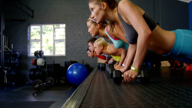Group of people performing push-up with kettlebell video