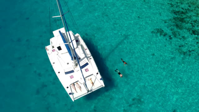 group of people relaxing and snorkeling from luxury catamaran video