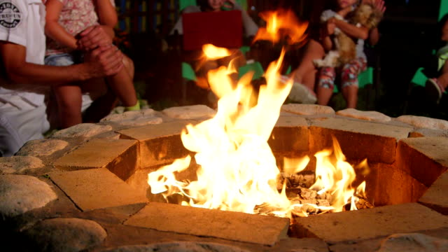 Group of people sitting on patio loungers around stone fire pit in back yard video