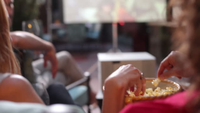 Group of people watch movie outdoors and eat popcorn video