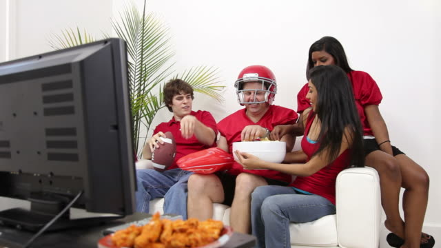 Group of people watching football game video