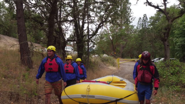 Group of people white water rafting carry raft video