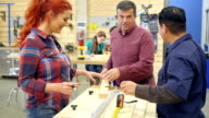 Group of people work together measuring wood in community woodworking workshop video