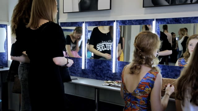 Group of pretty girls prepares for fashion show in dressing room video
