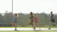 Group of runners running a race on a track in the city video