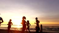 Group of runners working out by the sea during sunset video