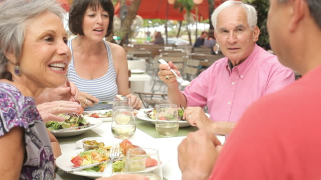 Group Of Senior Friends Enjoying Meal In Outdoor Restaurant video