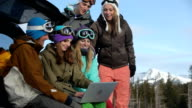 Group of snowboarders watch videos on laptop computer video