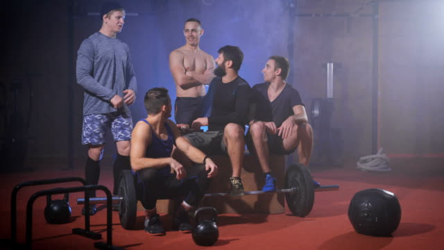Group of strong men at the gym having gun after gym training video