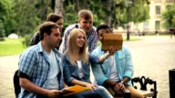 Group of students saying hi to friend using tablet video