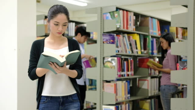 A group of students study and teenage friends reading in library. video